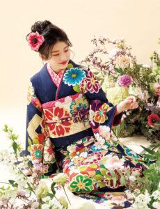 レトロ調の柄行を現代風の色選びで表現したデザインの妙。深みある藍の地に彩り豊かな花々や亀甲が配され、明るい笑顔で周囲を癒やします。